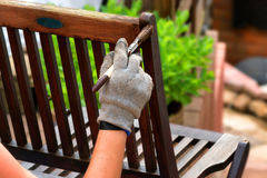 Women hand with brush strokes wooden furniture Royalty Free Stock Photography