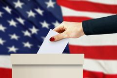 Women hand casting a vote. With american flag background Stock Image