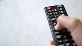 Women hand changes the channels on the TV remote control stock video footage