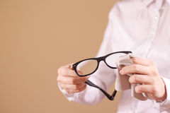 Women hand cleaning glasses lens with isolated background Stock Image