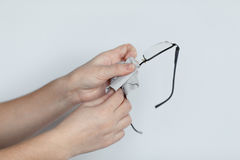 Women hand cleaning glasses lens with isolated background. Stock Photo