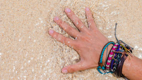 Women Hand with Colourful Wristband Toching Wet Sand on the Beach.  Stock Photography