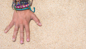 Women Hand with Colourful Wristband Toching Wet Sand on the Beach. Vertical orientated Stock Photo