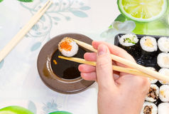 Women hand eating fresh sushi with chopsticks Royalty Free Stock Images