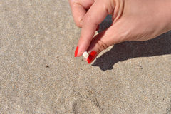 Women hand extinguish cigarette into the sand of a beach. Quitti Royalty Free Stock Images