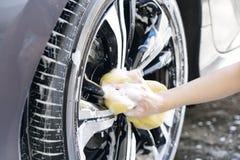 Women hand with foam sponge washing car wheel Royalty Free Stock Photo