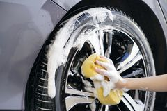 Women hand with foam sponge washing car wheel Royalty Free Stock Images
