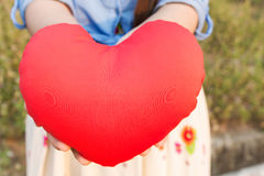 Women hand gently hold red heart with love, careness and restpec Stock Photos