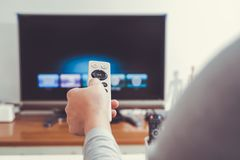 A women hand hold the remote control of the TV box in the living room Royalty Free Stock Photos