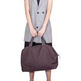 Women hand hold the travel bag, brown color on white background, Stock Photography