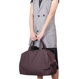 Women hand hold the travel bag, brown color on white background Stock Photos