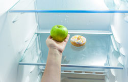 Women hand holding apple instead of donut in refrigerator Stock Photos