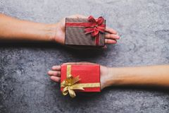Women hand holding brown gift box And a red gift box given to each other on a gray stone table. And daylight stock image