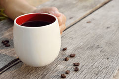Women  hand holding a coffee cup. Women hand  holding a coffee cup on wood background Stock Image