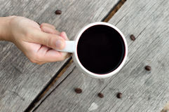 Women hand holding Cup of coffee. On wooden table background Royalty Free Stock Photo