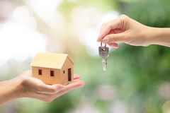 Women hand holding a model home and a key, Buying a new house con royalty free stock image