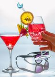 Women hand holding one of cocktail glasses decprated with tropic royalty free stock photos