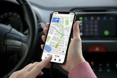 Women hand holding phone with app navigation map on screen. In the car stock images