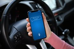 Women hand holding phone with app personal assistant on screen. In the car stock photography