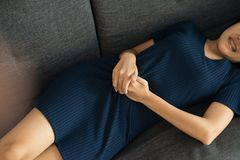 Women hand holding on stomach suffering from abdominal pain,Female with having menstrual period cramp,Food poisoning,Close up. Woman hands holding on stomach royalty free stock image