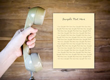 Women hand holding Telephone Receiver with note paper Stock Photo