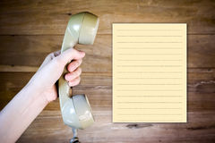 Women hand holding Telephone Receiver with note paper Stock Image