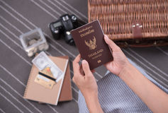 Women hand holding Thailand travel passport with camera, money b Royalty Free Stock Images