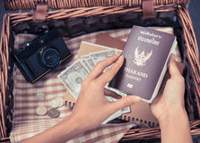 Women hand holding Thailand travel passport with camera, money Royalty Free Stock Images