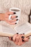 Women hand holds piece of paper of book, she is in sweater. Young Girl hand with black nails manicure holds book and tea cup, woman in wool sweater reading Royalty Free Stock Photos