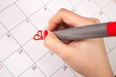 Women hand with pencil drawing heart shape in calendar for Valentines day. Young female hand with pencil drawing hearts shape and words in calendar reminder for Royalty Free Stock Photos