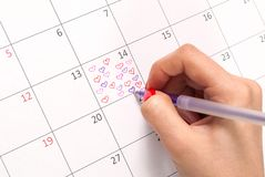 Women hand with pencil drawing hearts shape in calendar for Valentines day. Young female hand with pencil drawing hearts shape and words in calendar reminder for Royalty Free Stock Image
