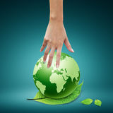 Women hand pointing down to the green globe Royalty Free Stock Image