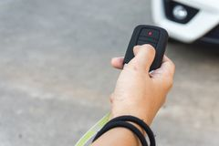 Women hand presses on the remote control car alarm system Royalty Free Stock Photos