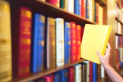 Women hand pulling yellow book from wood bookshelves in public library. Colorful books, Textbook, Literature on bookshelf. royalty free stock photos