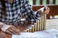 Women hand put money coins to stack of coins. Business Growth co. Ncept royalty free stock photos