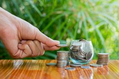 Women hand put money coins to stack of coins. Business Growth concept Royalty Free Stock Images