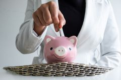 Women hand putting coin into pink piggy bank saving money with coins bunker stock image