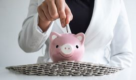 Women hand putting coin into pink piggy bank saving money with coins bunker stock photos