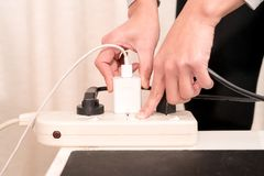 Women hand putting the electric plug while switching on the electricity supply connection Royalty Free Stock Photos