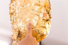Women hand putting gold leaf onto The Buddha statue to gild. Which people use to worship the Buddha image royalty free stock photography
