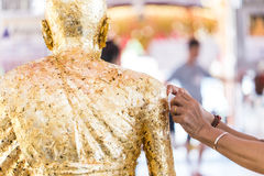 Women hand putting gold leaf onto The Buddha statue to gild. Royalty Free Stock Images