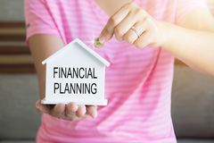 women hand putting money coin in piggy bank with Financial Planning word, Saving money concept, concept of financial savings to b stock photography