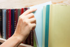 Women Hand selecting book from a bookshelf in library. Back to school. Royalty Free Stock Images