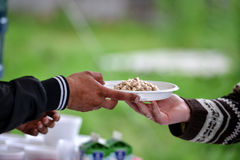Women hand serving another person a plate with food. Royalty Free Stock Image
