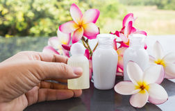 Women hand taking small bottle of spa shampoo or shower gel with plumeria or frangipani flower Royalty Free Stock Photos