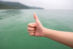 Women hand with thumb up  on green sea Stock Image