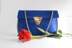 Women handbag. Women blue handbag and red rose Stock Photos