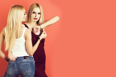 Women twins, friends with bright makeup. Women in handcuff, fashion cloth posing on pink background, pretty blonde girl friends, twins sisters having bright royalty free stock photography
