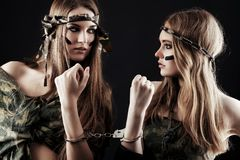 Women in handcuffs. Two sexy women in military uniform posing against black background Stock Image