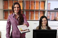 Women handing over dvd at the video rental store. Happy women handing over dvd at the video rental store Stock Images
